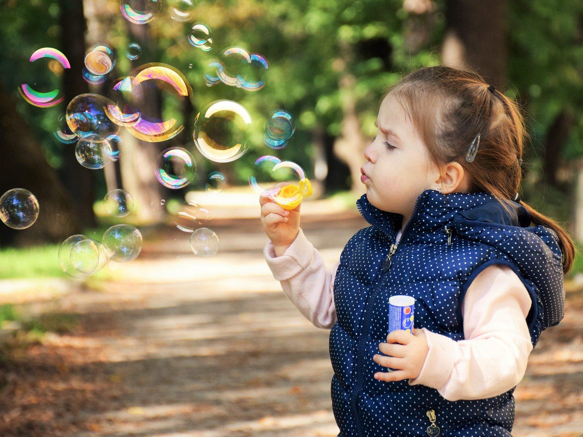 na zdjęciu dziewczynka puszczająca bańki