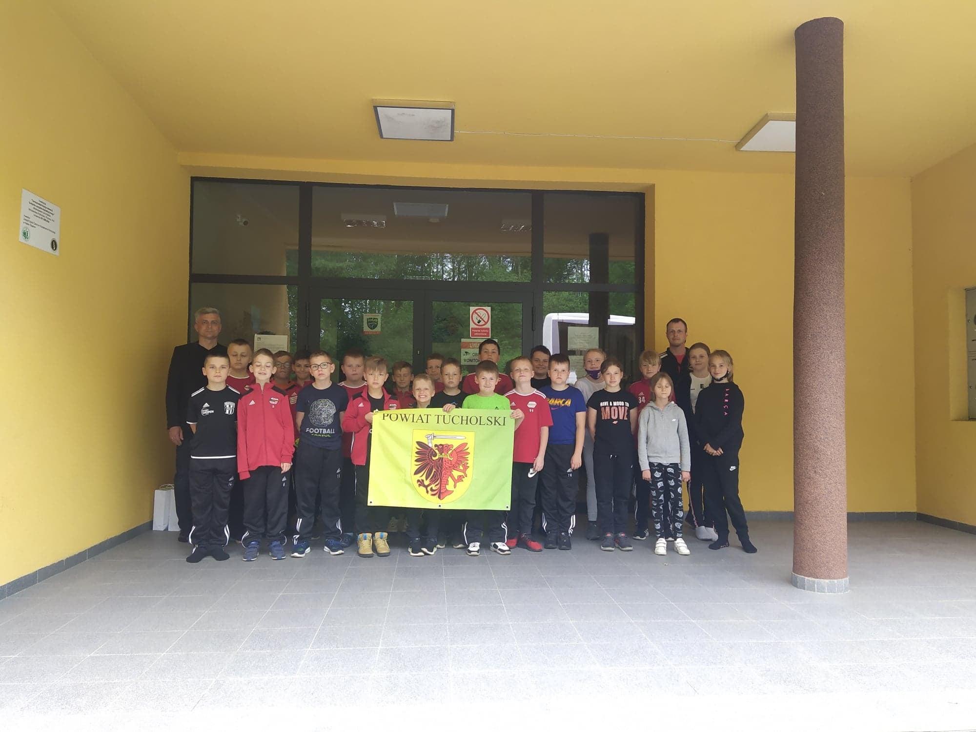 na zdjęciu grupa dzieci z powiatu tucholskiego z flagą z herbem Tucholi