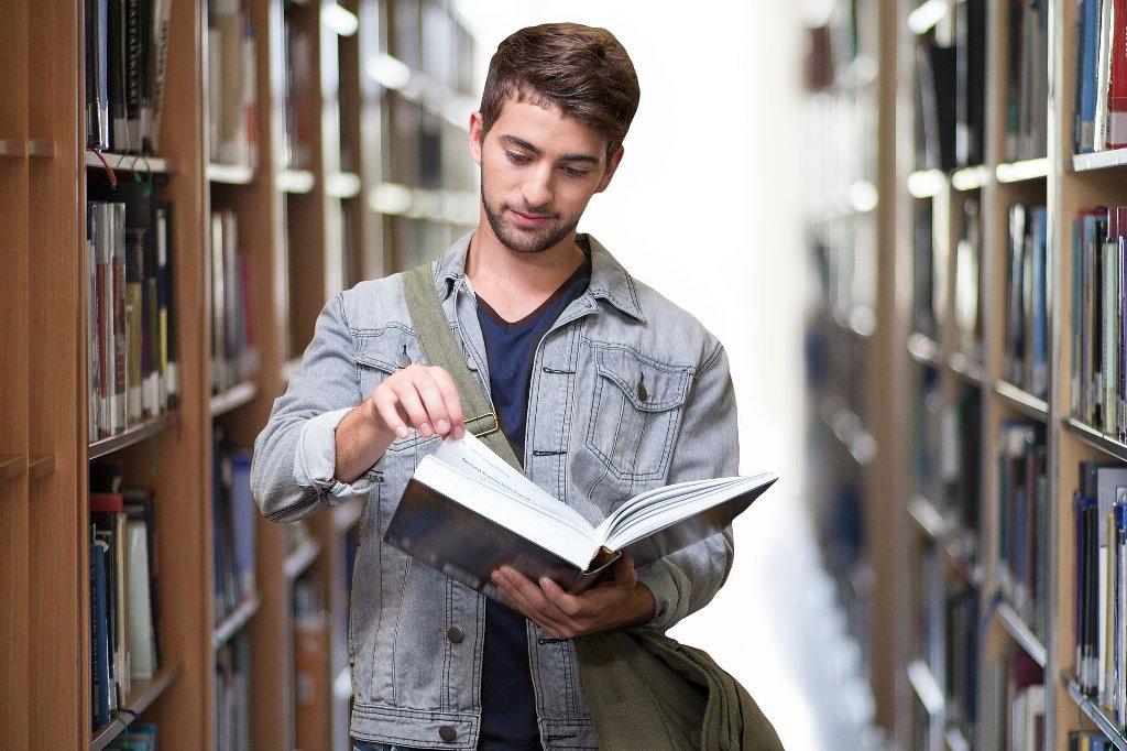młody mężyzna stoi pomiędzy regałami z ksiązkami, w rękach trzyma otwartą ksziążkę,