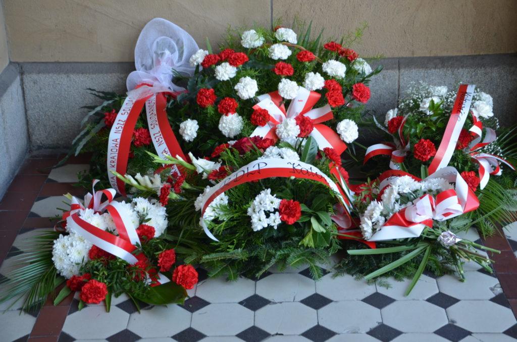 kwiaty złożone pod tablicą