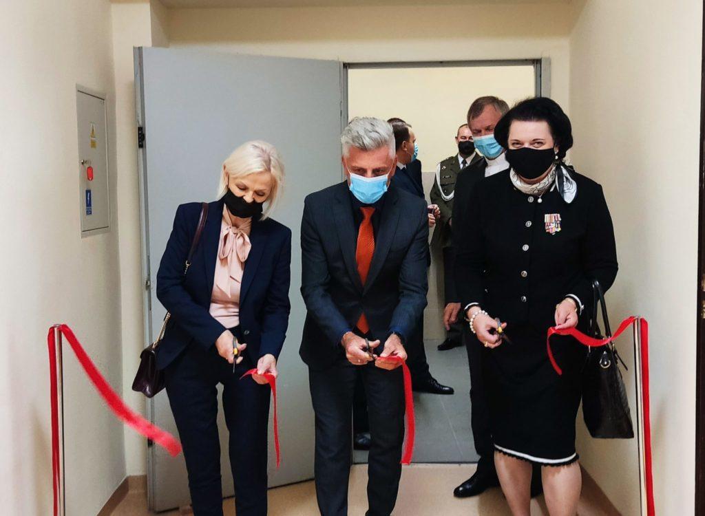 trzy osoby, nożyczkami symbolicznie przecinają wstegę