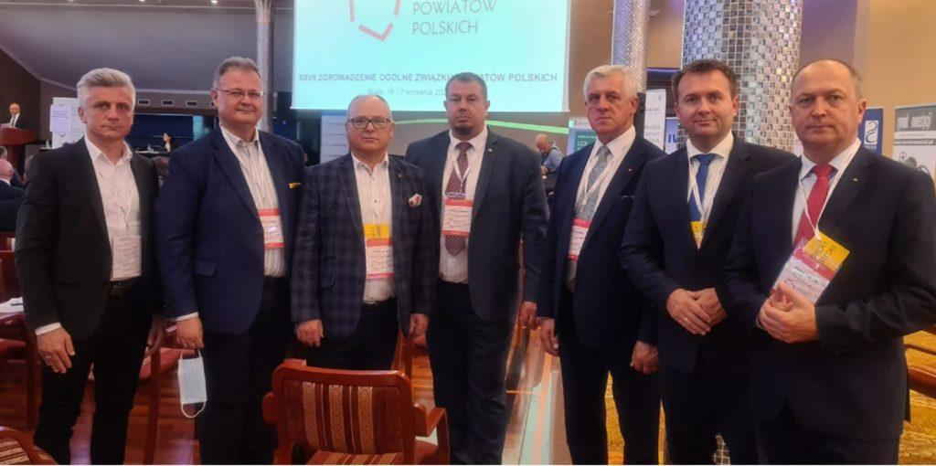 Wicestraosta Sebasain Nowak w towarzystwie kilku mężczyzn, wszczyscy w ciemnych garniturach
