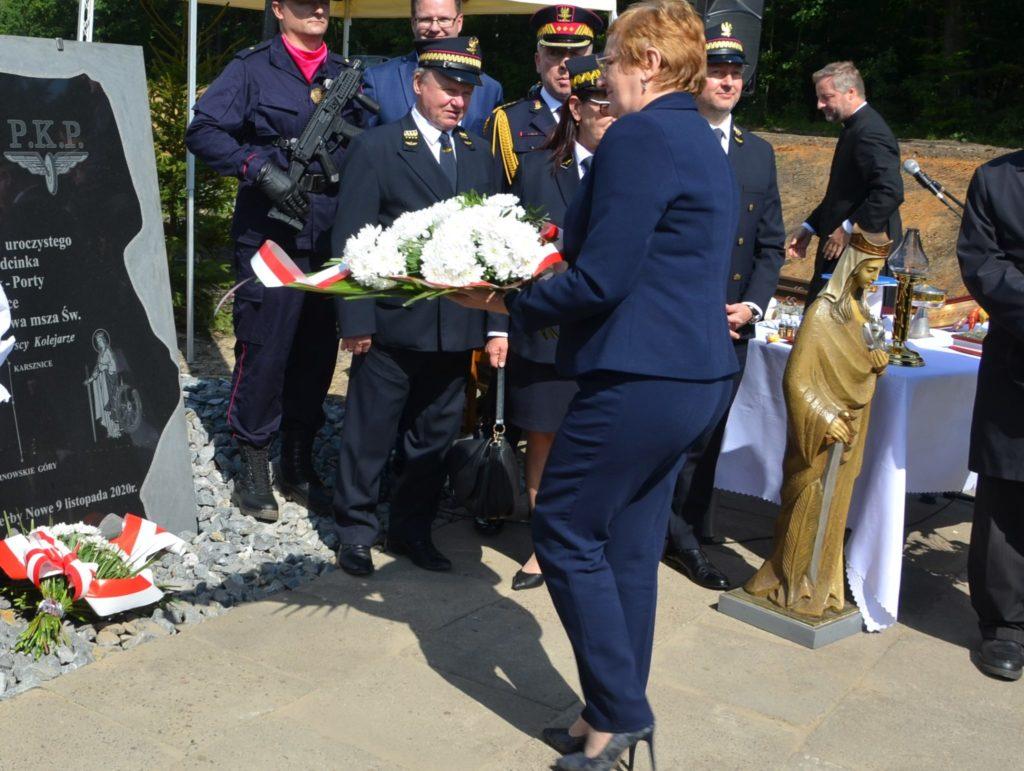 Starosta składa kwiaty pod pamiątkową tablicą