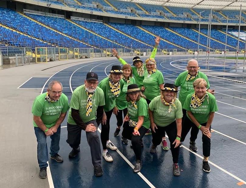 dzeisięć osób w koszulkach zielonego koloru na bieżni satdionu