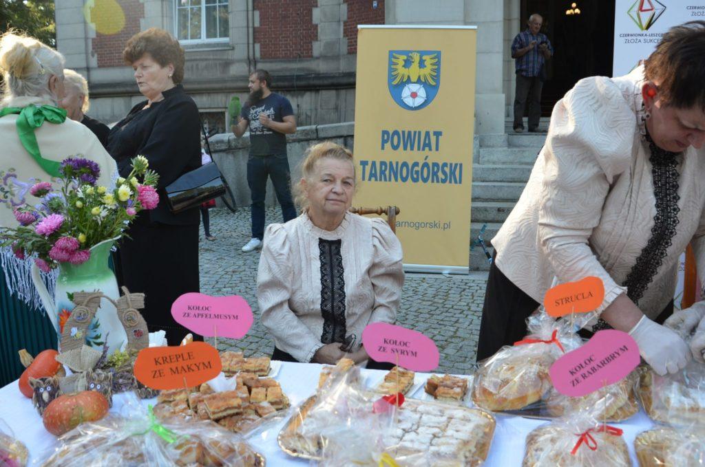 kobieta siedzi na krześle, przed nią stolik z ciastem, w tle baner Powiat Tarnogórski
