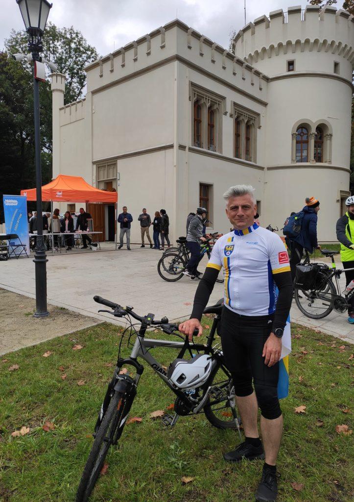 Sebastian Nowak ubrany na sportowo obok roweru