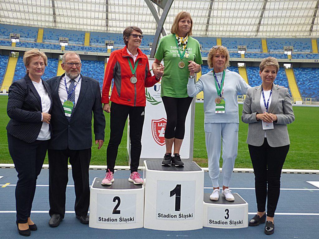 kilka osób, trzy stoją na podium , pierwsze, drudie i trzecie miejsce, na bieżni stadionu