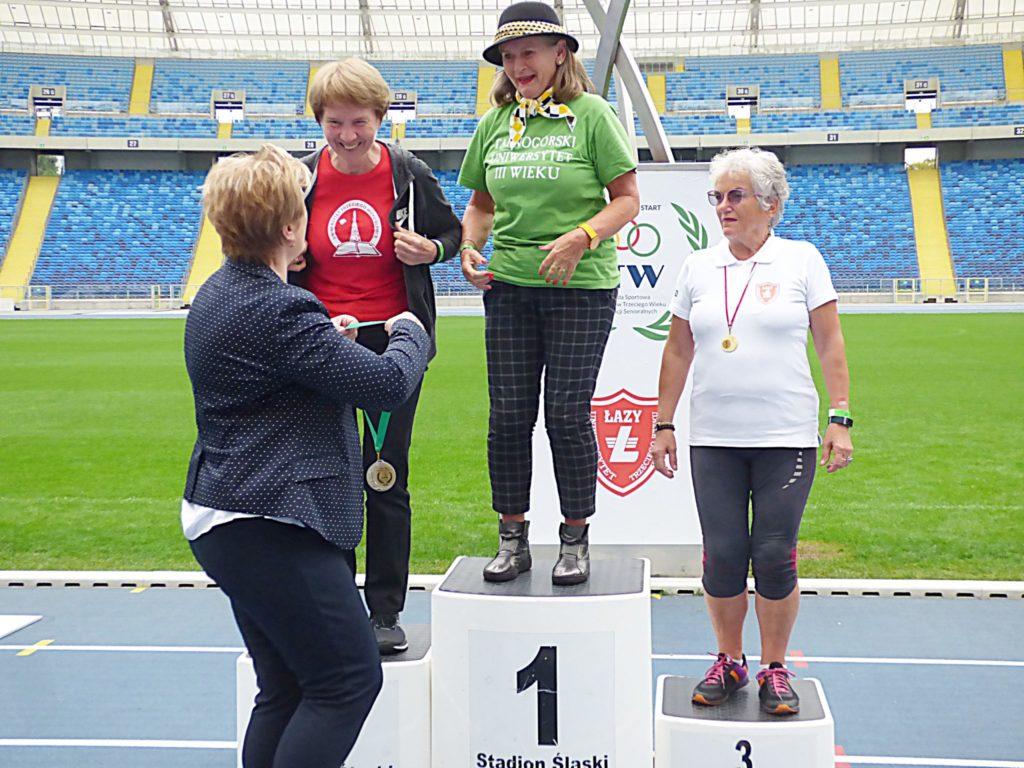 ceremonia wręczania medali, kilka osób, jedna wręcza medal uczestniczce,