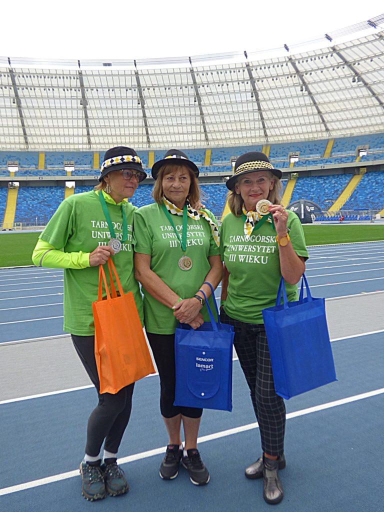 trzy kobiety w zielonych koszulkach z torbami, na głowach mają kapelusze, miejsce stadion,