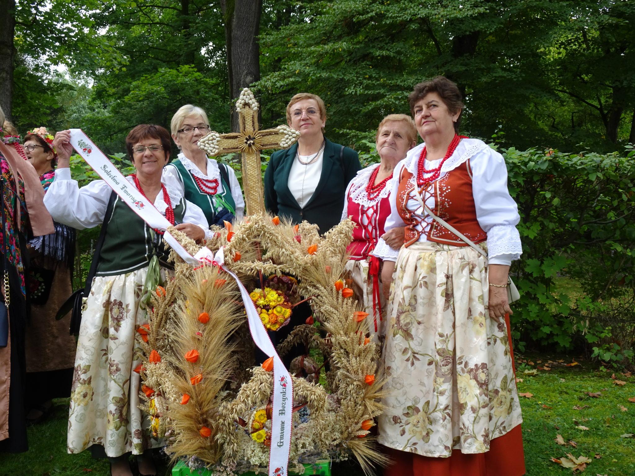 Starosta Krystyna KOsmala wraz z kilkoma paniami ubranymi w stroje ludowe prezentują koronę dożynkową