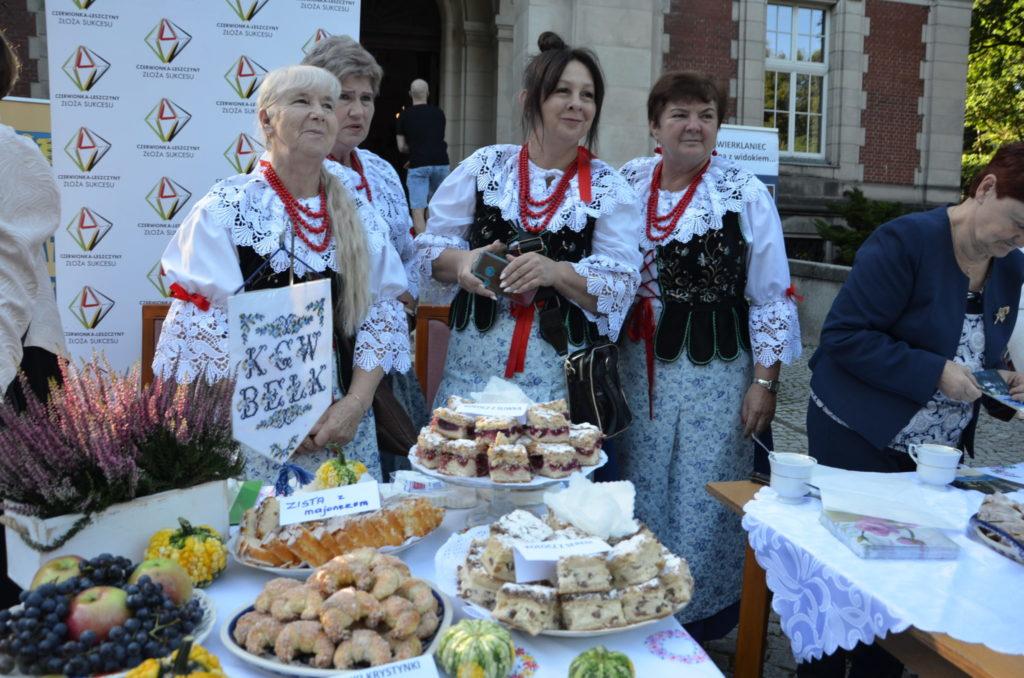 trzy kobiety w strojach ludowych na stoliku ciasto