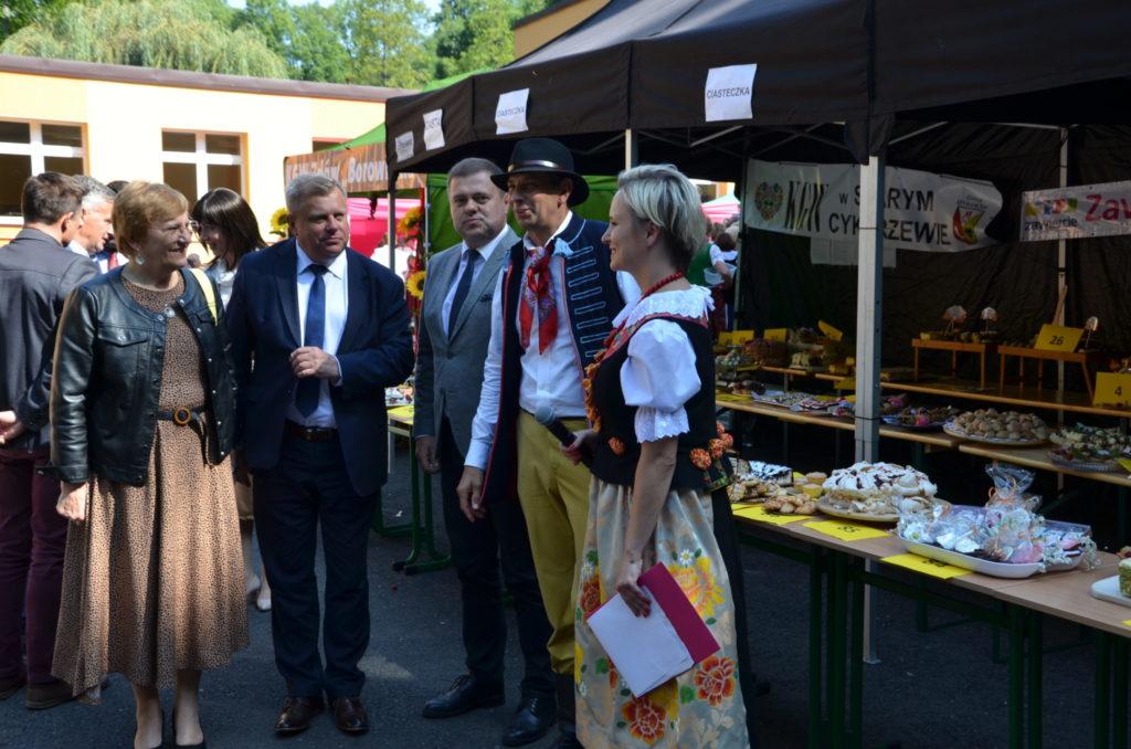 grupa kilku osób obok stoiska z ciastami