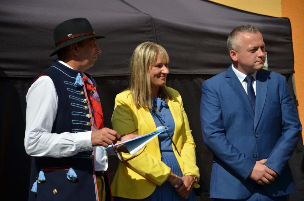 trzy osoby, dwóch mężczyzn w śrenim wieku posrodku kobieta w żółtej marynarce,