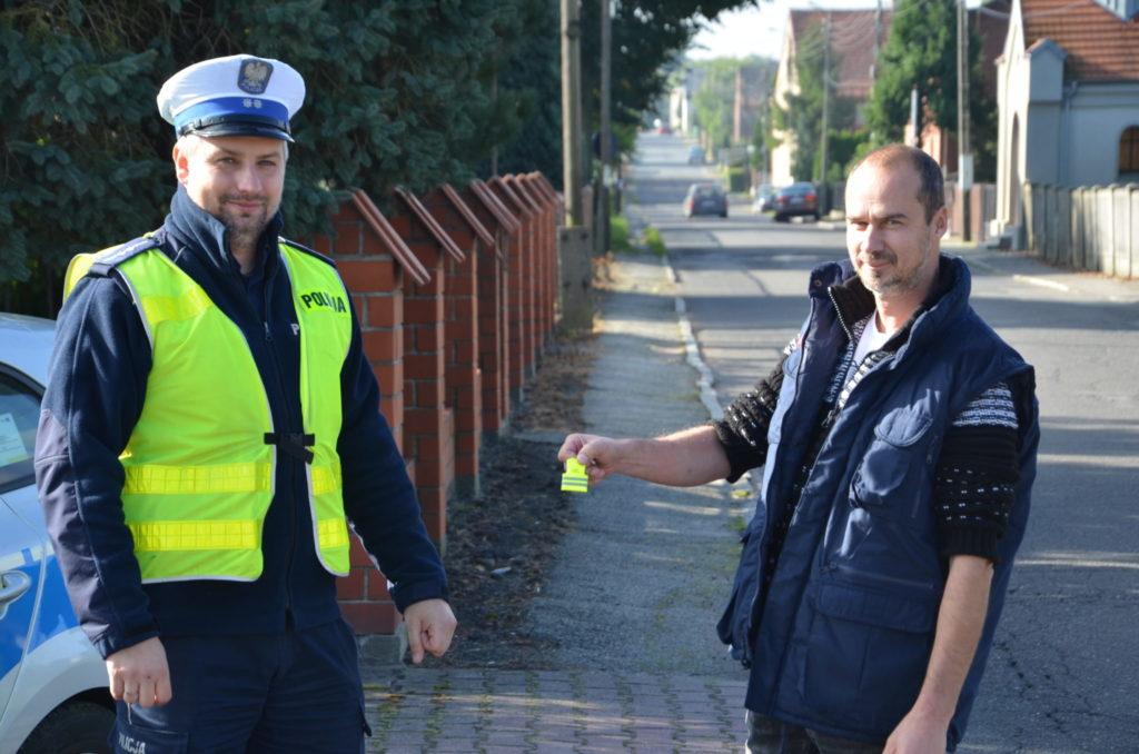 na chodniku przy drodze policjant ruchu drogowego przekazuje odblask mężczyźnie,