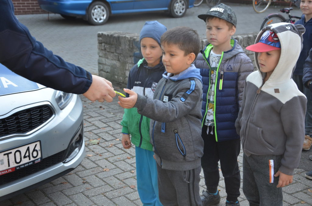 grupa kilku małych chłopców odbierają odblaski