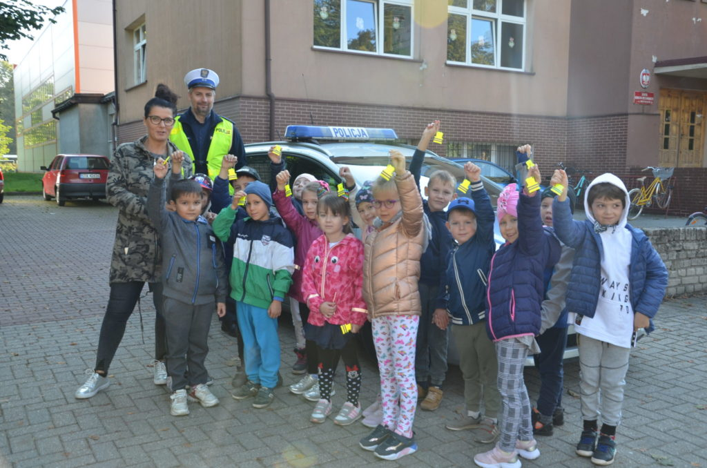 grupa dzieci z przedszkola wraz z policjantem pozują do zdjęcia na tle radiowozu