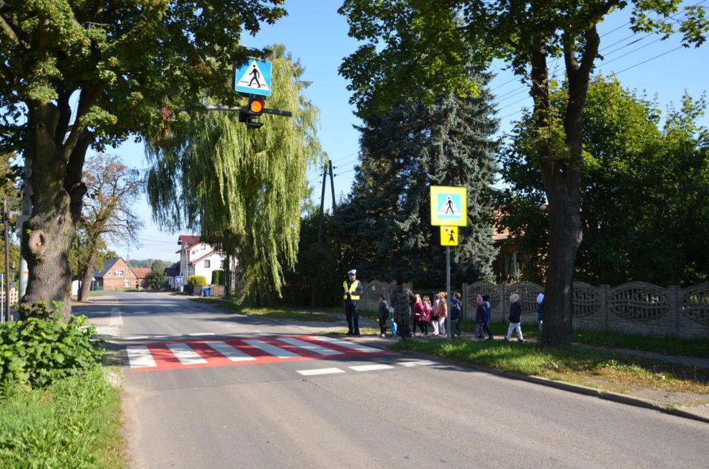 droga z przejściem dla pieszych, obok stoją dzieci wraz z policjantem drogówki