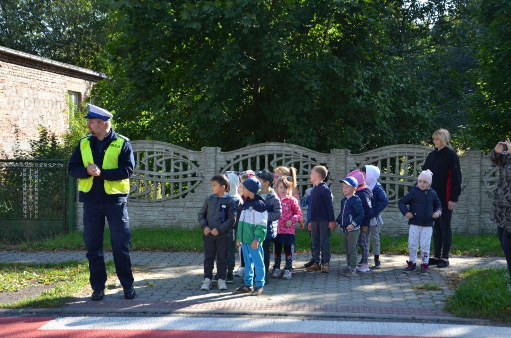 policjant uczy dzieci przechodzić przez jezdnię