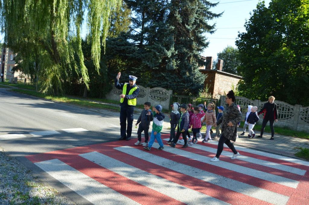 grupa przedszkolaków przechodzi przez jezdnie w asyście policjanta i opiekunki