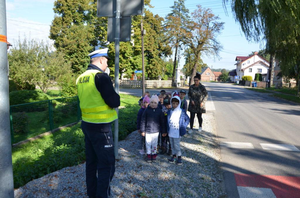 na chodniku stoją policjant drogówki i dzieci z przedszkola