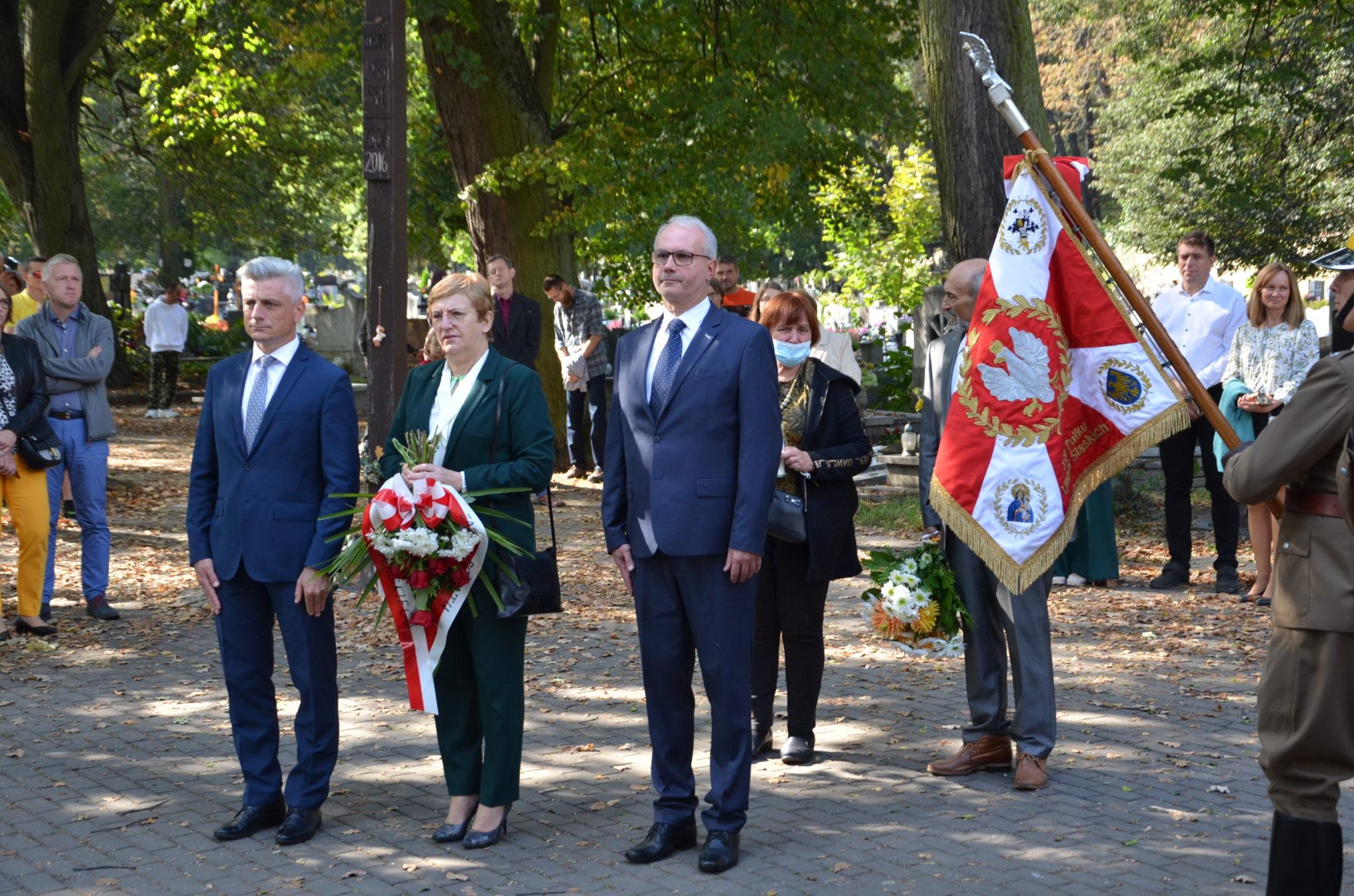 Krystyna Kosmala Starosta Tarnogórski w rękach trzyma kwiaty,obok stoją Krzytof Łoziński, Sebastian Nowak,
