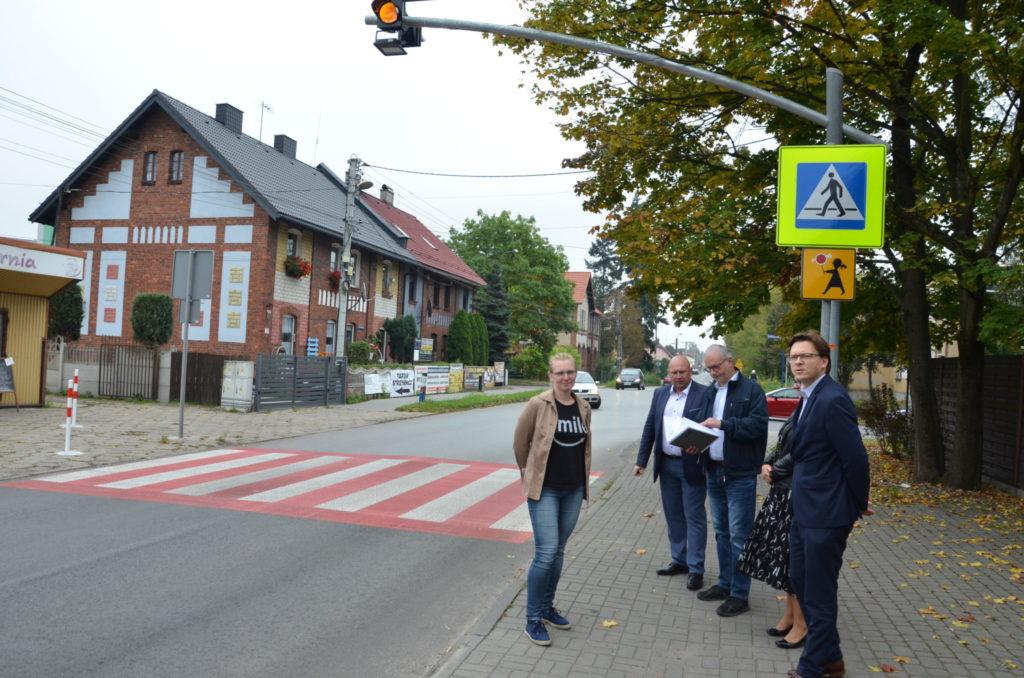 Kilka dorosłych osób i rozmawia, za nimi znaki ostrzegawcze przejscie dla pieszych