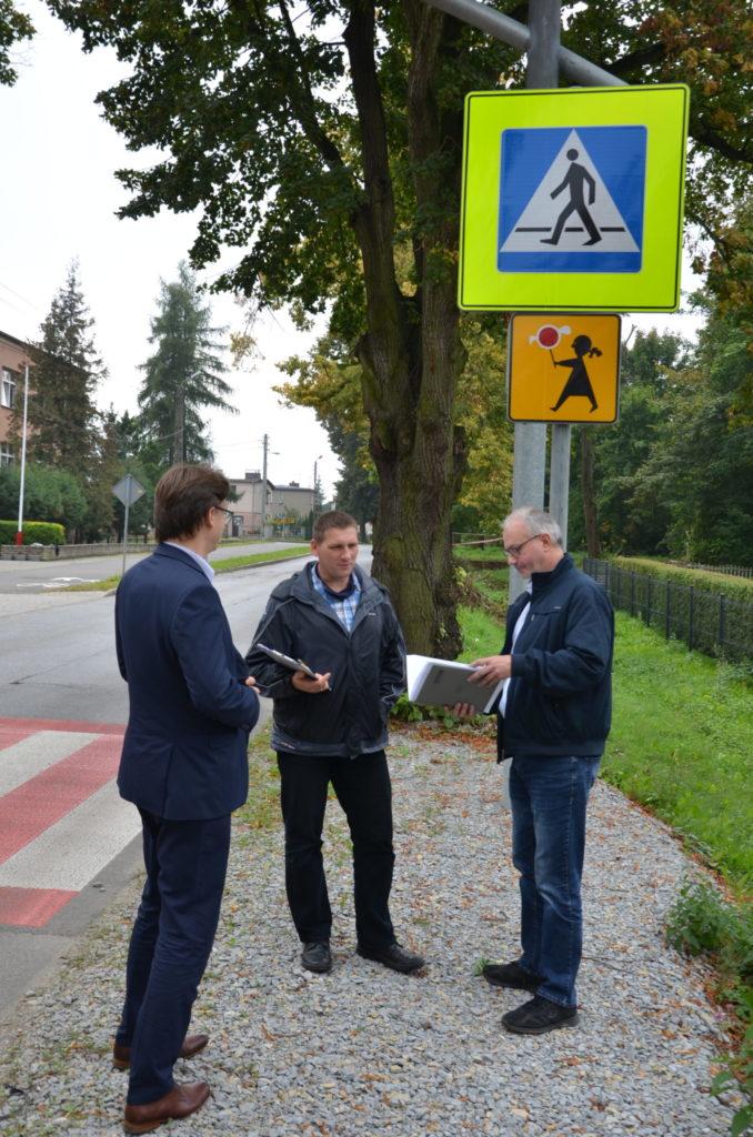 trzech mężczyn romawia ze sobą obok przejscia dla pieszych, przeglądając dokumentację