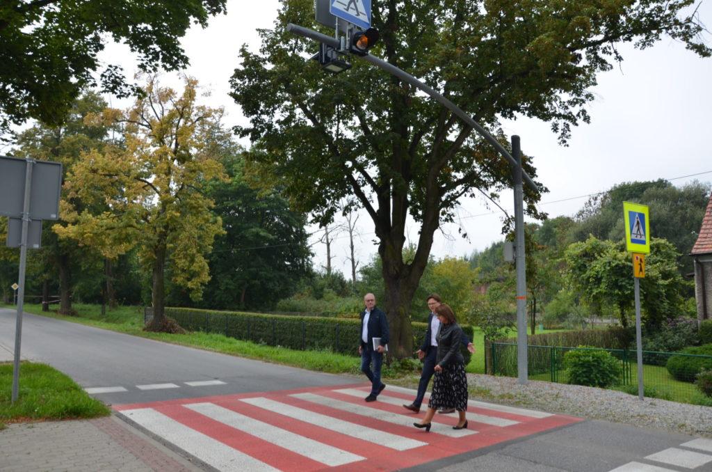 trzy osoby dorosłe przechodzą przez przejście dla pieszych