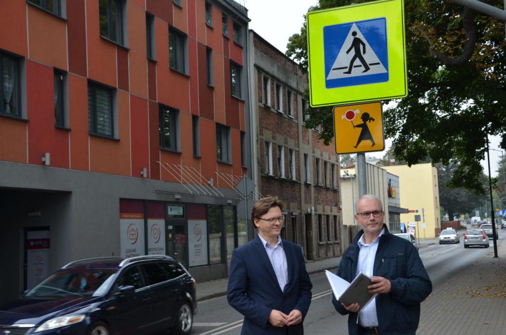 Krzysztof Łoziński oraz Stanisłąw Torbus przy przjeściu dla piezych za njimi znaki drogowe uwaga przejście
