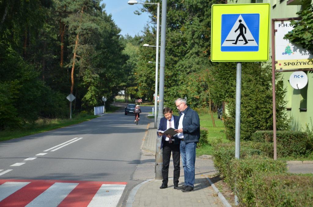 dwóch mężczyzn przegląda dokumnetację, stoją obok przejscia dla pieszych