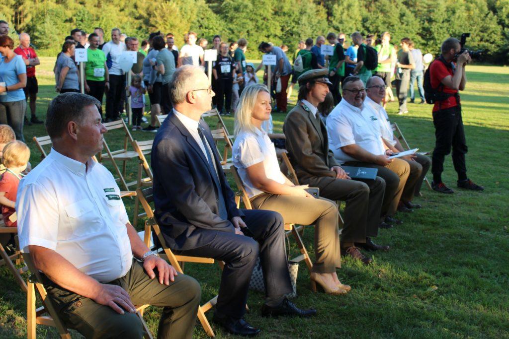 klika osób siedzących na krzesłach, za nimi kilkadziesiąt osób