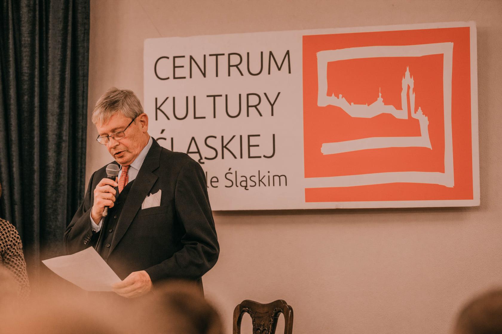 mężczyzna w ręku trzyma mikrofon w tle tablica Centrum Kultury Śląskiej