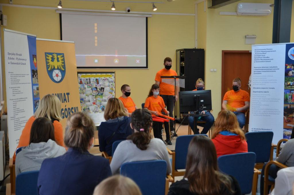 młode osoby w pomarańczowych koszulkach wysteują przed publicznością