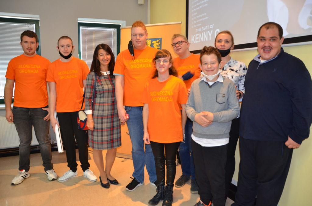 grupa soób w pomarańczowych koszulkach wraz ze swoją wychowawczynią