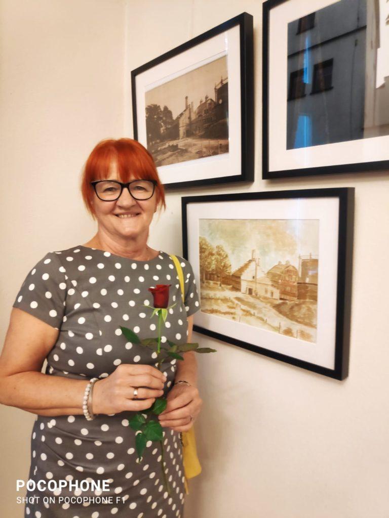 kobieta w średnim wieku, rude włosy, w okularach, w sukience w białe kropki, w ęeku rzyma różę, obok na ścianie wisza obrazy,