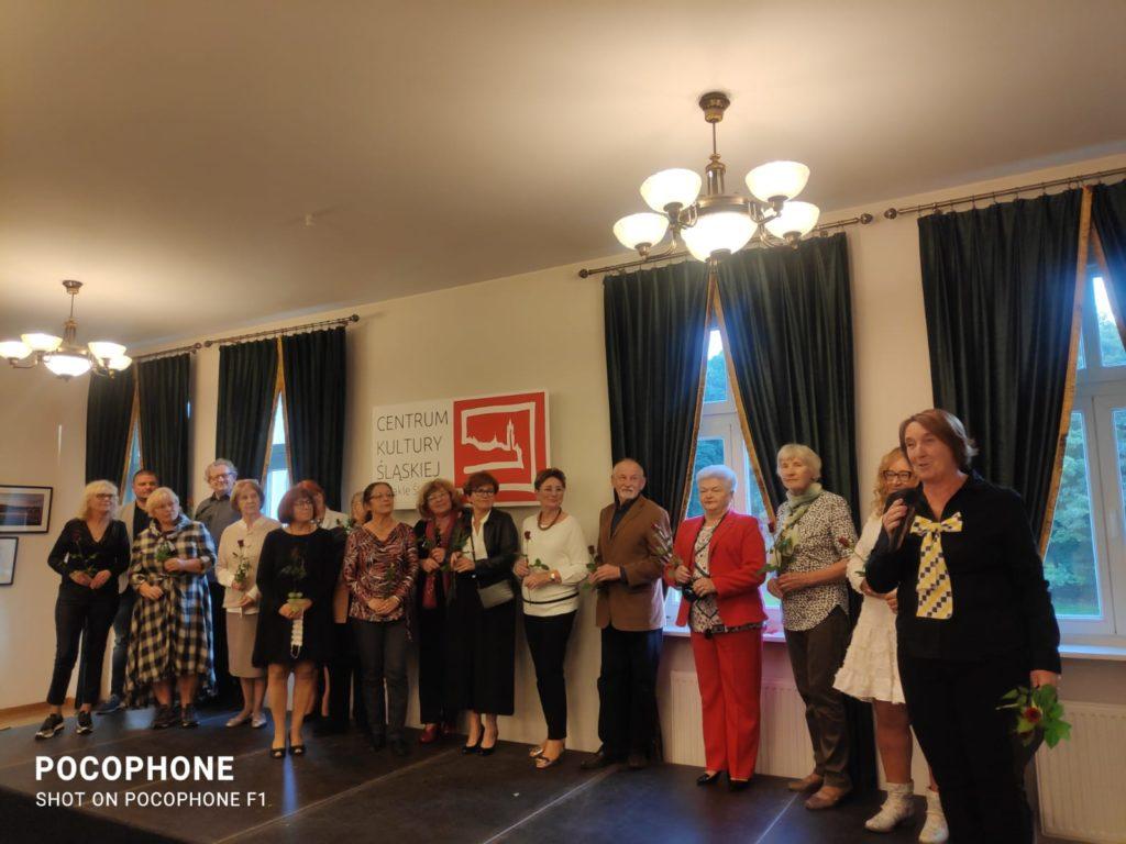 kilkanaście kobiet stoi z różami w ręku podczas wernisażu