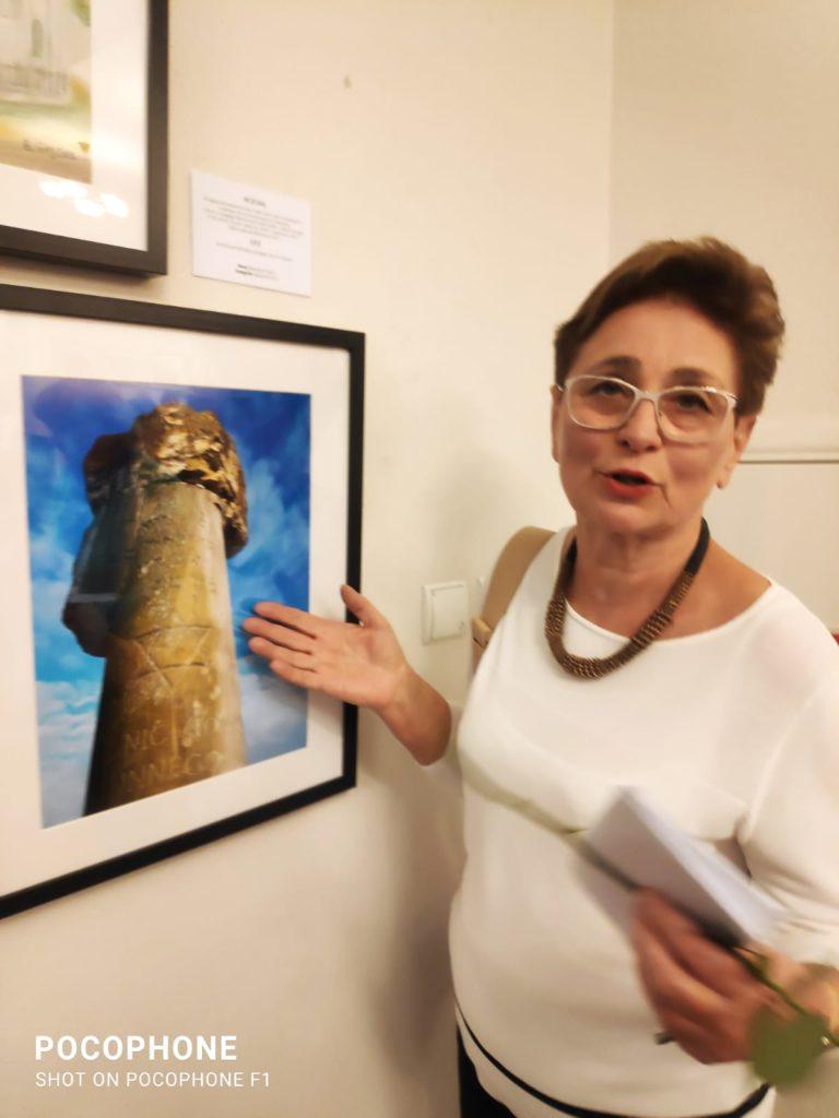 kobieta w średnim wieku, w okularach, krótkie rude włosy, stoi wskazując jedną ręką obraz,