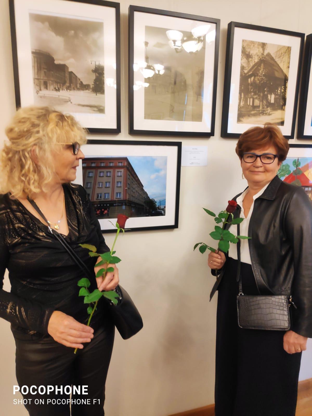 dwie kobiety stoją obok siebie, w rękach trzymają róże, kobiety w średnim wieku, jedna blondynka w okularach, druga włosy ciemne, także w okularach,