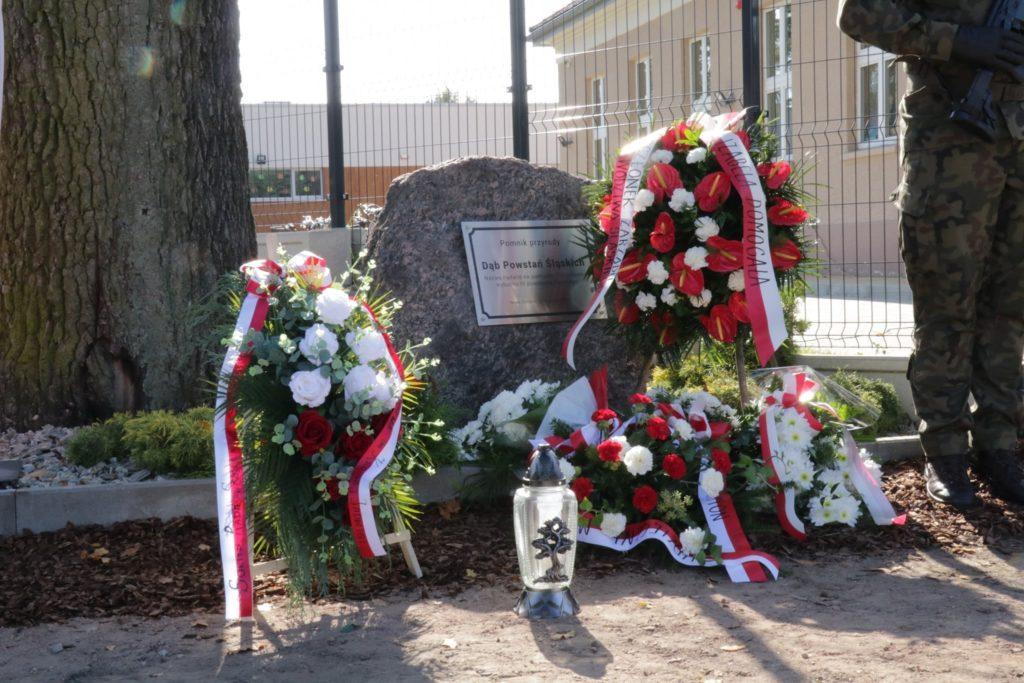 kamień z tabliczką z grawerem  obok kwiaty