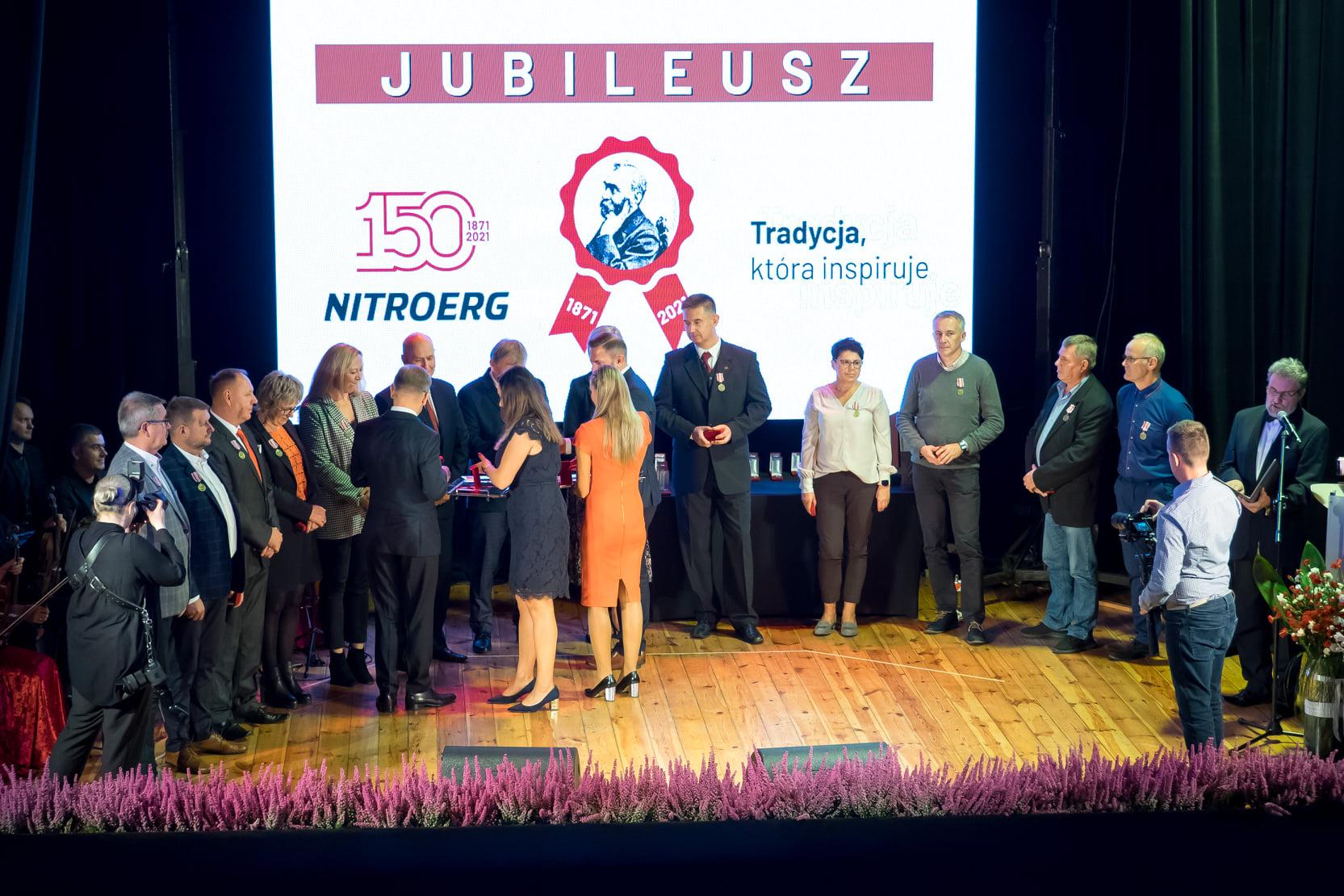 grupa osób stoi na scenie za nimi na ścianie logo firmy