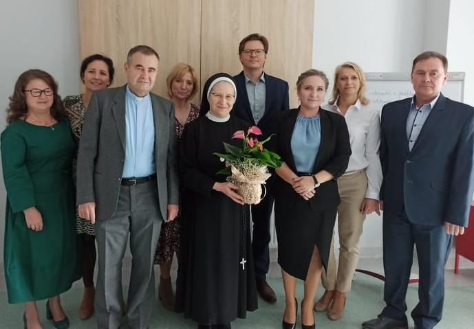 kilka osób, pośrodku stoi siostra zakonna w ręku trzyma kwiatki