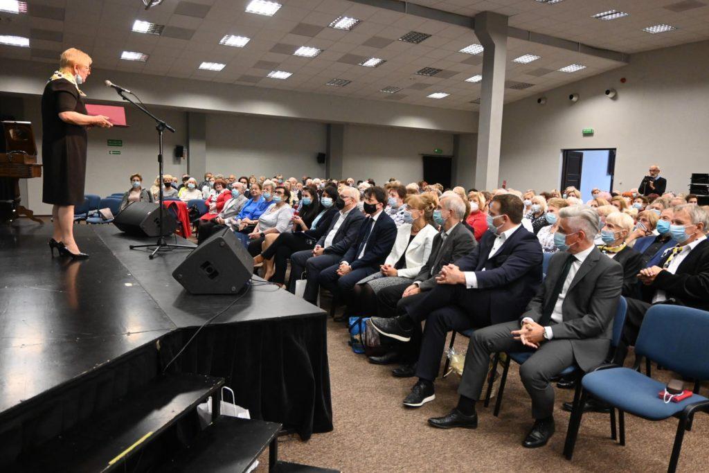 kilkadzisiat osób siedzi na krzesłach w sali