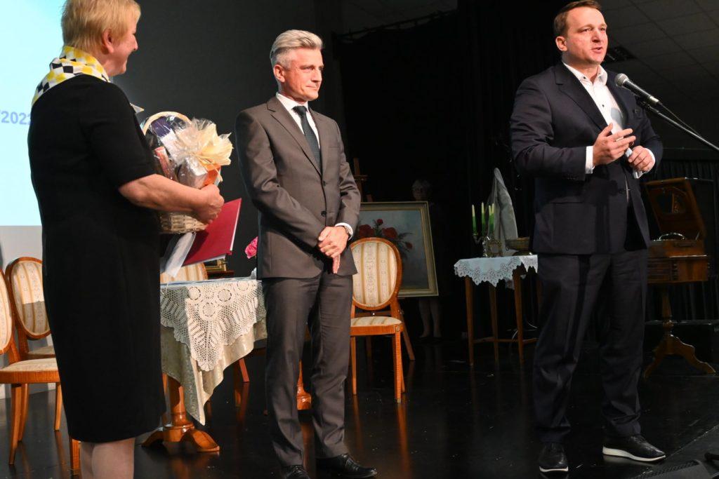 Wicestarosta I Przewodniczący skladają kwiaty kobiecie