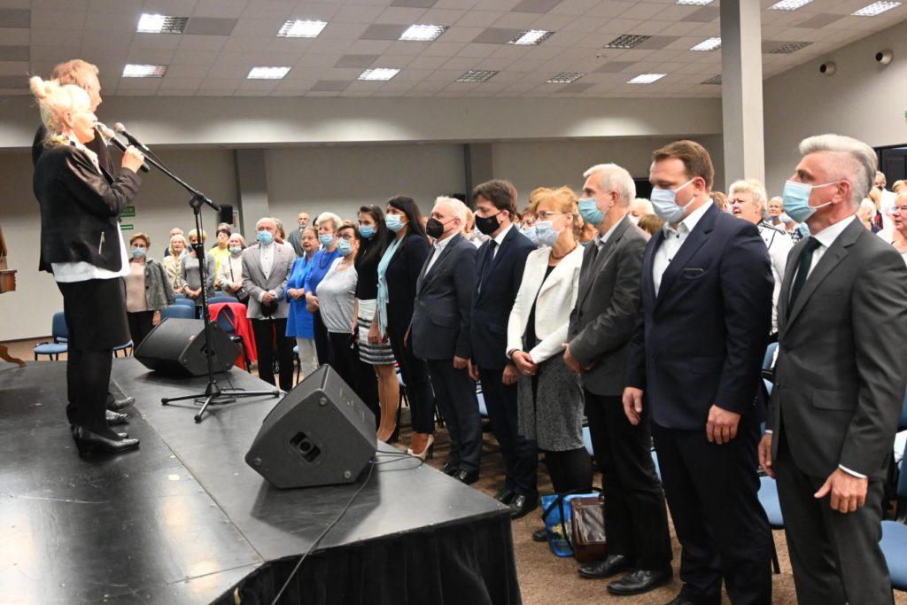kilkanaście osób stoi na sali przed sceną
