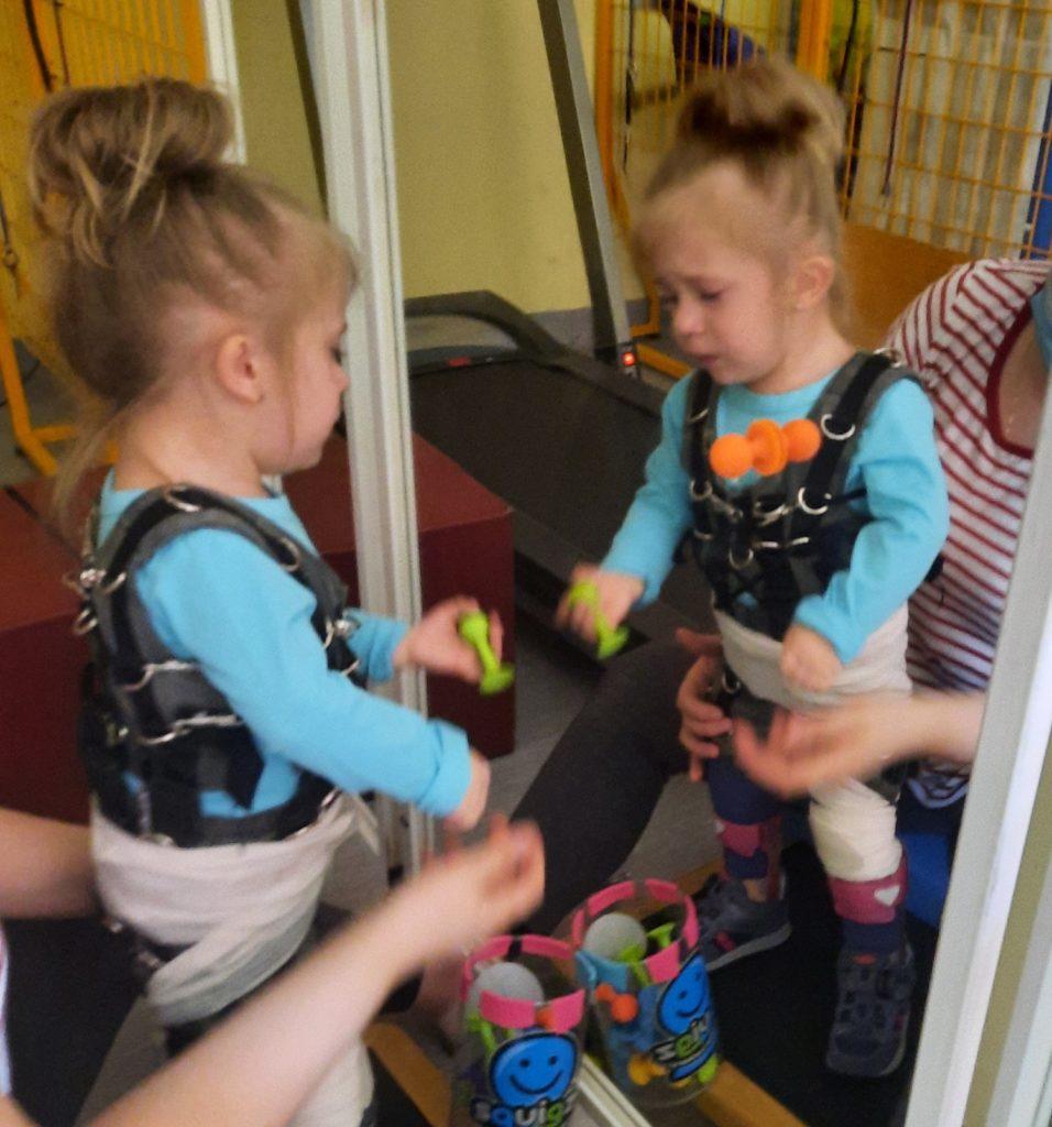 dziewczynka przed lustrem uczy się chodzić w specjalnej ortopedycznej uprzęży